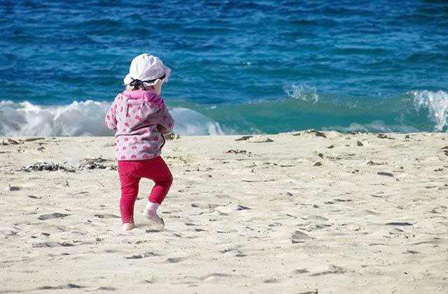 Ein Kind am Strand muss gut vor UV Strahlen geschützt werden